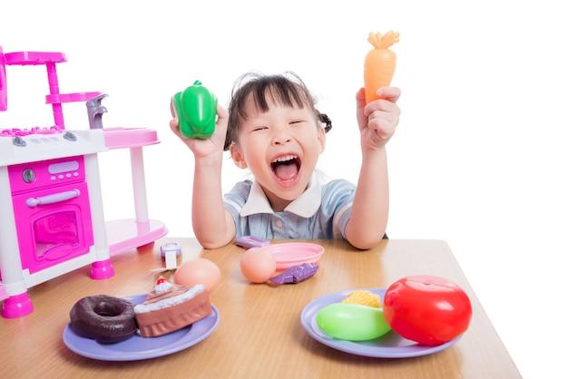 Menina asiática que joga com o brinquedo da cozinha sobre o fundo branco