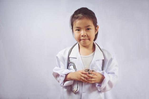 Menina asiática que joga como um dinheiro do cuidado do doutor no copo