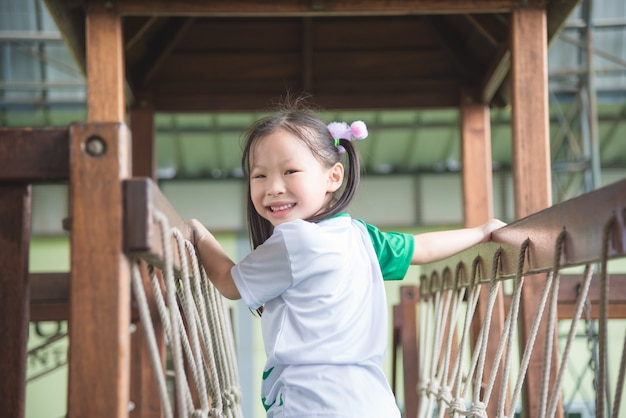 Menina asiática que joga e sorri no campo de jogos da escola