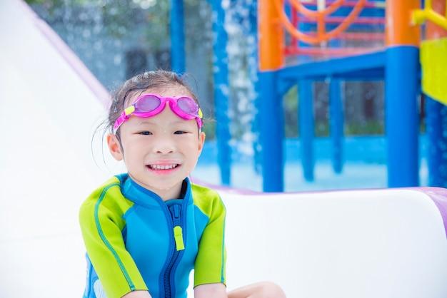 Menina asiática que joga e sorri no parque da água