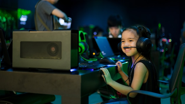 Menina asiática que joga jogos de computador no café do internet