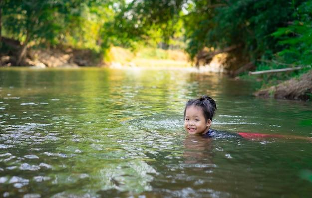 Menina asiática que joga no rio com luz solar