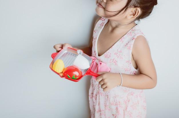 Menina asiática que joga o cozimento do brinquedo.