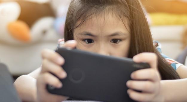 Menina asiática que joga o jogo no telefone móvel com cara do sorriso.