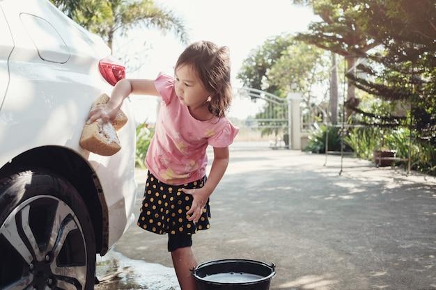 Menina asiática que lava um carro em casa