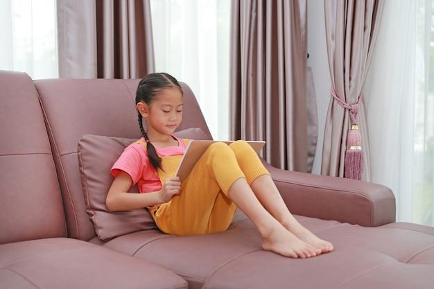 Menina asiática que lê um livro deitado no sofá em casa