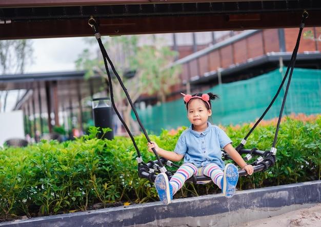 Menina asiática que senta-se em um balanço no campo de jogos das crianças