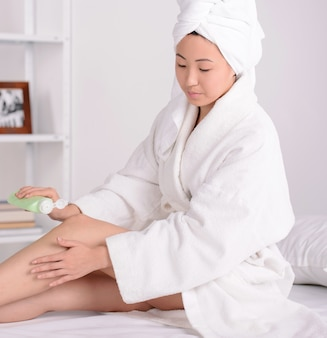 Menina asiática que senta-se em uma cama nas toalhas.