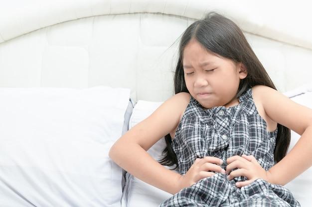 Menina asiática que sofre de dor de estômago