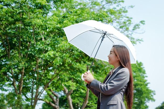 Menina asiática que trabalha no escritório ela segurava um guarda-sol no clima quente.