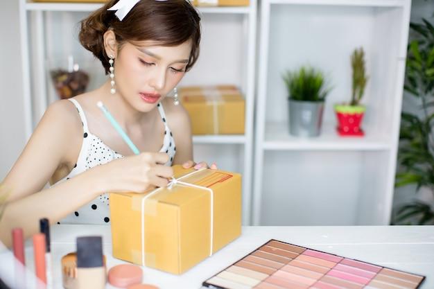 Menina asiática que trabalha no escritório home e que classifica a caixa do cargo para o serviço de entrega ao cliente