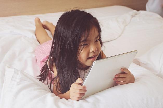 Menina asiática que usa o computador tablet na cama