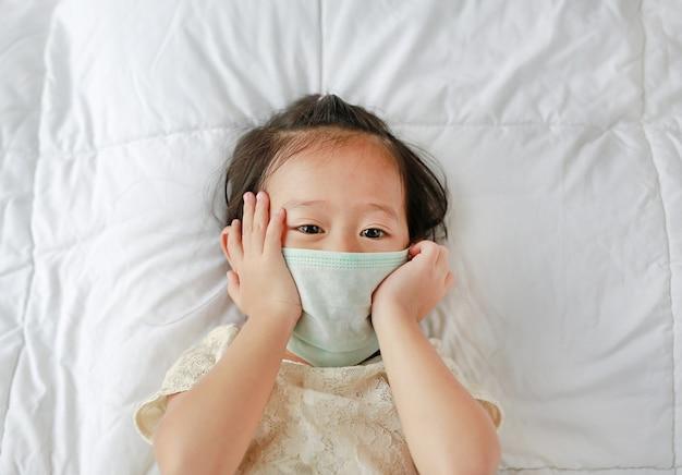 Menina asiática que veste uma máscara protetora que encontra-se na cama.