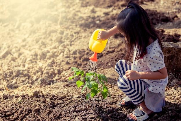 Menina asiática regando uma árvore jovem com vaso de água no tom de cor vintage
