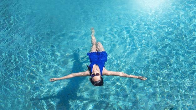 Menina asiática relaxando nadando na piscina