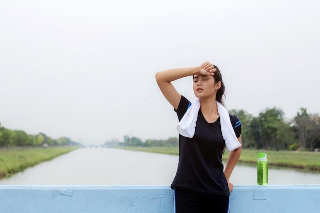 Menina asiática relaxando no parque com o céu.