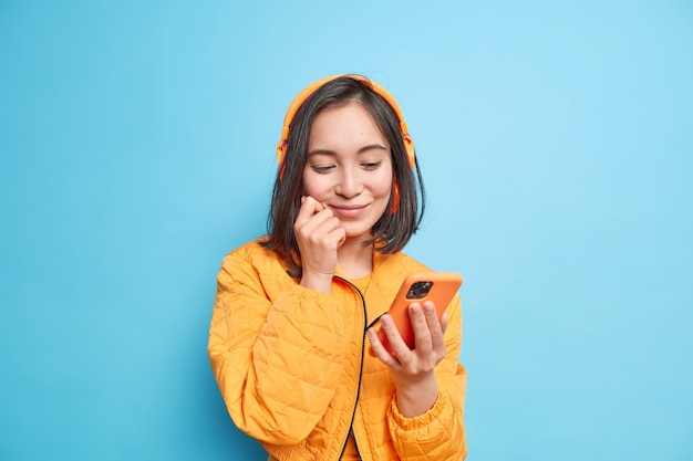 Menina asiática satisfeita com cabelo escuro focada na tela do smartphone escolhe faixa de áudio da lista de reprodução e usa fones de ouvido estéreo sem fio nas orelhas vestida com jaqueta laranja isolada sobre a parede azul