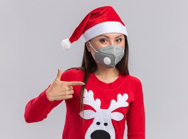 Menina asiática satisfeita com um chapéu de natal com suéter e máscara médica apontando para o lado isolado no fundo branco com espaço de cópia