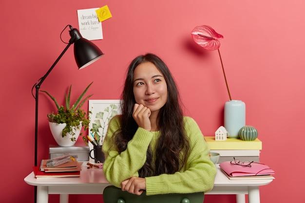 Menina asiática satisfeita se senta contra a mesa com todos os suprimentos necessários para estudar, sorri e sonha acordada durante as férias, posa na cadeira contra uma parede rosada brilhante, notas adesivas com inscrição.