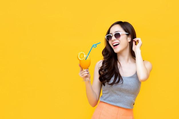 Menina asiática saudável com roupa de verão, bebendo suco de laranja