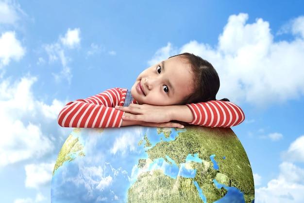 Menina asiática se apóia na terra. dia mundial da criança