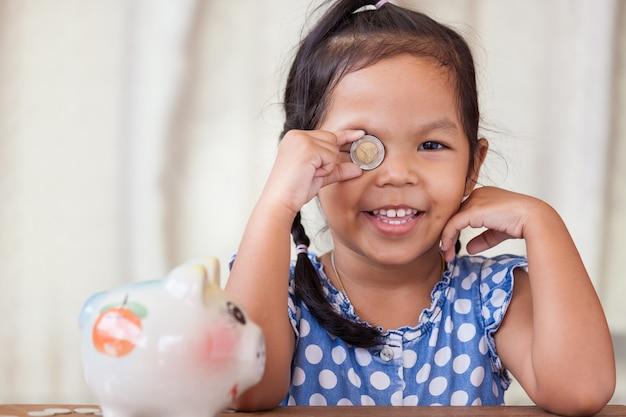 Menina asiática se divertindo brincando com uma moeda