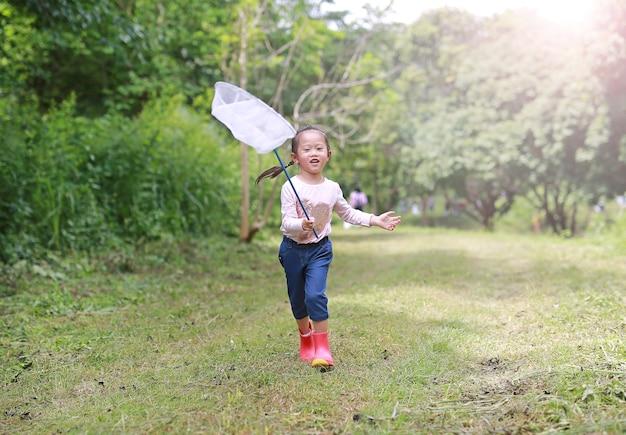 Menina asiática se divertindo com captura de insetos net