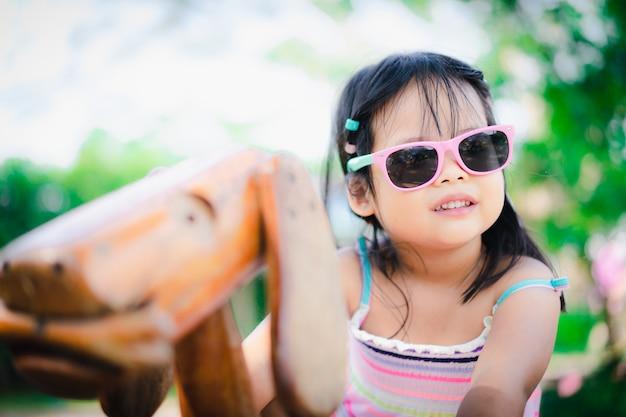 Menina asiática se divertindo na gangorra no playground