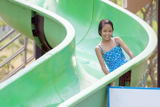 Menina asiática se divertir jogando um slide no parque aquático.