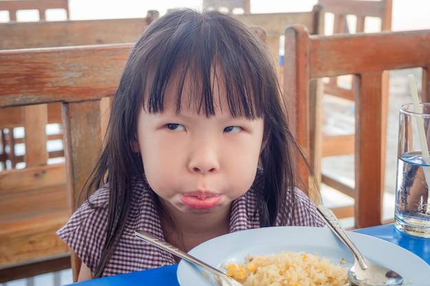 Menina asiática se recusando a comer arroz frito para o almoço