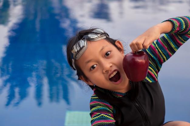 Menina asiática segurando a maçã na piscina com óculos de natação
