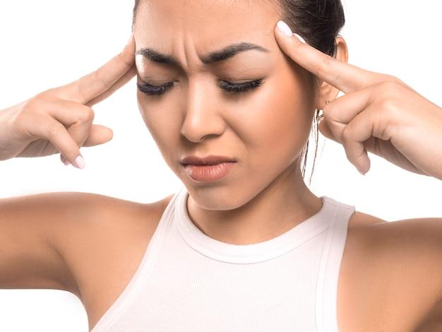 Menina asiática segurando as mãos sobre os templos. conceito de dor de cabeça. enxaqueca.