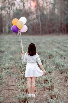 Menina asiática segurando balões em um campo.