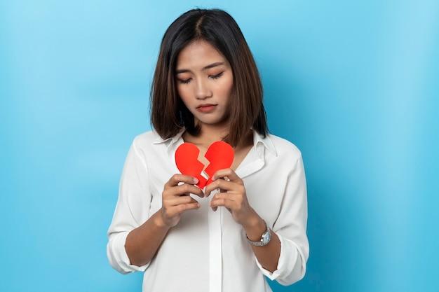 Menina asiática segurando formato de coração vermelho quebrado
