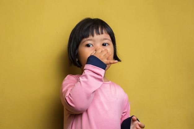 Menina asiática segurando o nariz por causa de um cheiro ruim