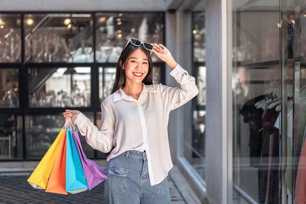 Menina asiática segurando sacolas de compras
