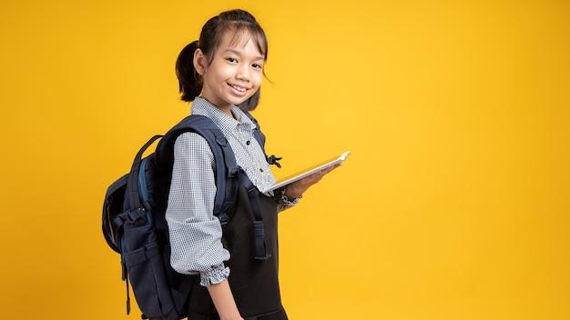 Menina asiática segurando tablet com mochila