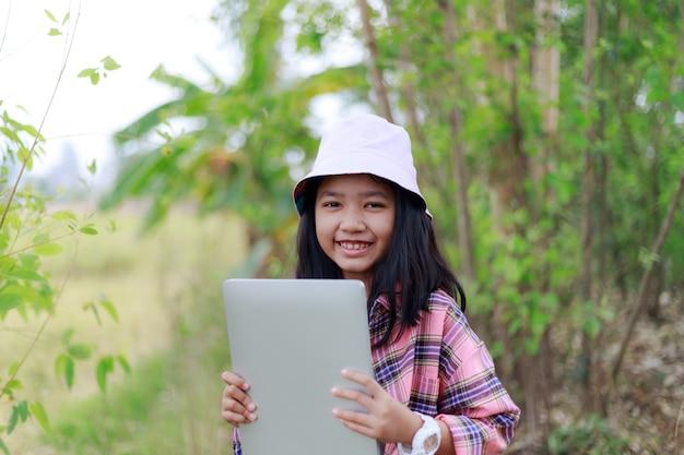 Menina asiática segurando tablet na fazenda tropical Foto Premium