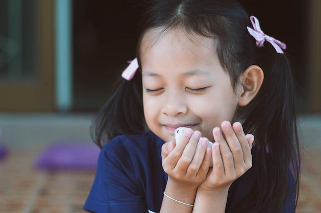 Menina asiática segurando um rato de estimação com amor e feliz