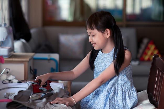Menina asiática sentada e passando a roupa na casa com um sorriso e feliz
