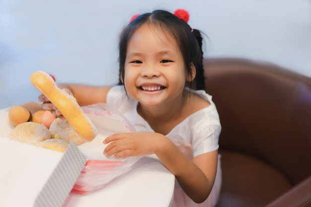 Menina asiática sentada na cadeira com segurando e comendo donuts