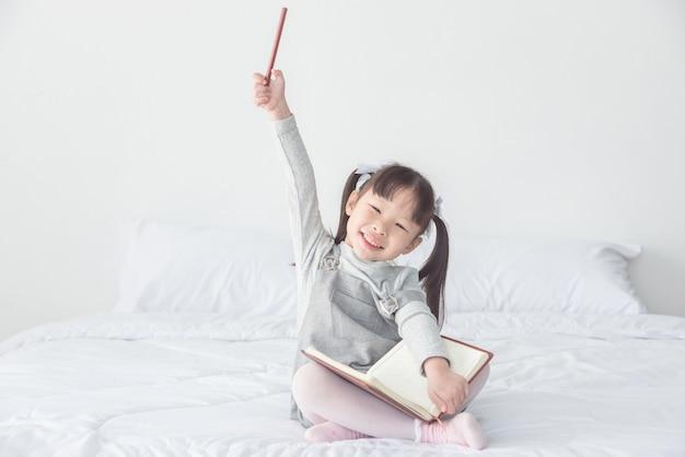 Menina asiática sentada na cama e sorrir enquanto segura o lápis e caderno
