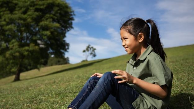 Menina asiática sentada na colina com grama verde para curtir a beleza da natureza no verão