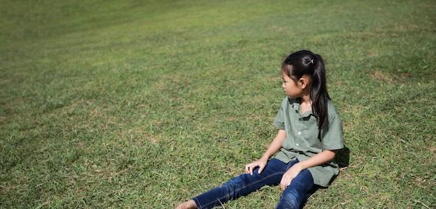 Menina asiática sentada na colina com grama verde para desfrutar da bela natureza