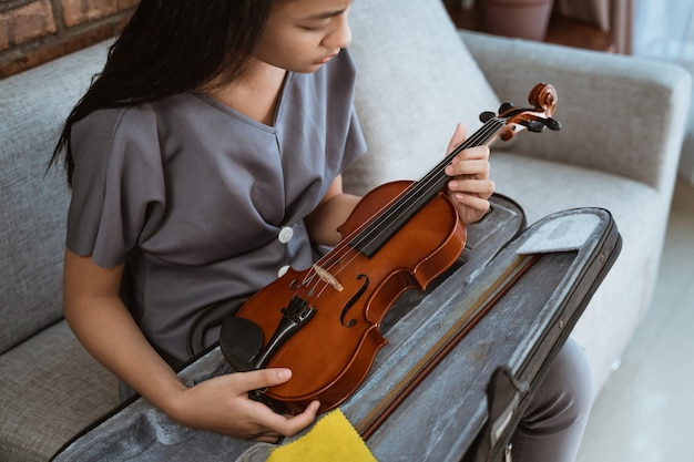 Menina asiática sentada no sofá segurando um violino