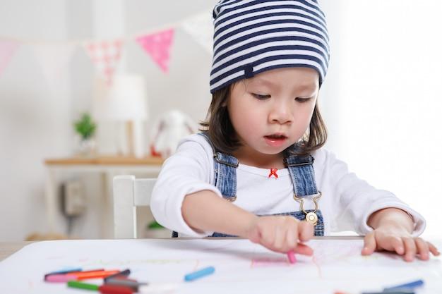 Menina asiática, sentado à mesa na sala, menina pré-escolar desenho em papel com canetas coloridas em dia ensolarado, jardim de infância ou
