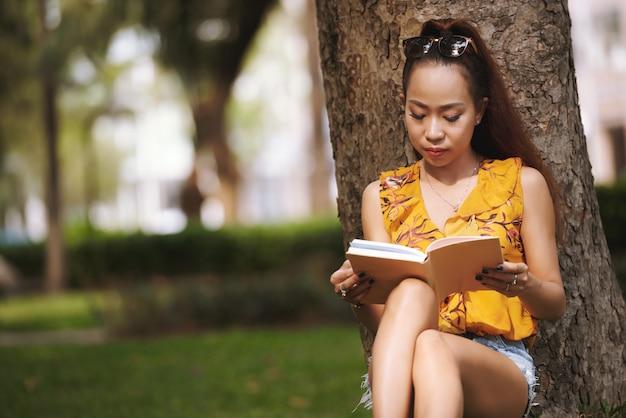 Menina asiática, sentado de costas contra a árvore no parque urbano e livro de leitura