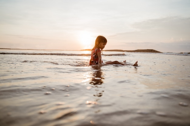 Menina asiática sentado na areia na praia enquanto brincava com água