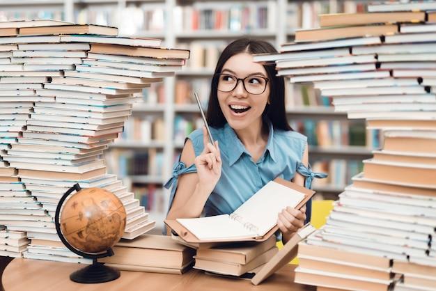 Menina asiática, sentando, tabela, cercado, por, livros, em, biblioteca