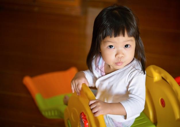 Menina asiática sente-se no controle deslizante em casa